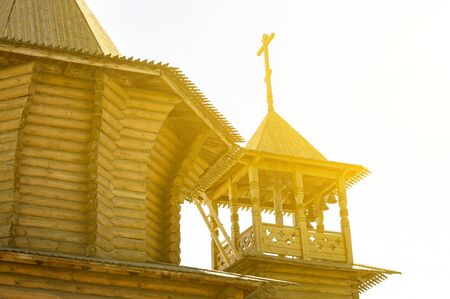 The bell tower and dome of a wooden Christian church in the sun. View from below. Stok Fotoğraf - 133322258