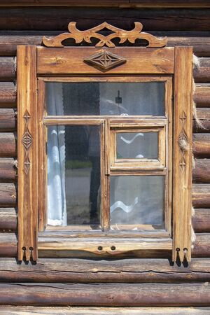 Window with carved platbands in an old wooden house. Stok Fotoğraf - 131246628
