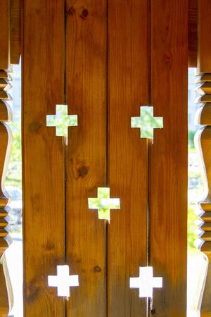 A wooden billboard made of boards with crosses on the porch of an old wooden orthodox church. Front view.