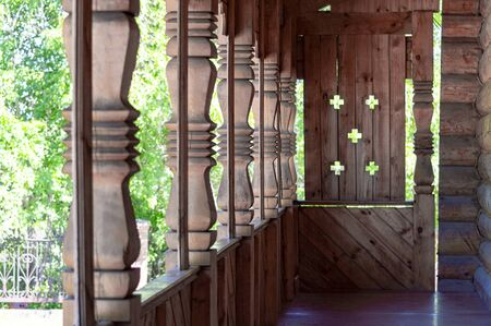 Wooden architecture. Fragment of the porch of an old Christian temple. Carved columns. View along. Stok Fotoğraf