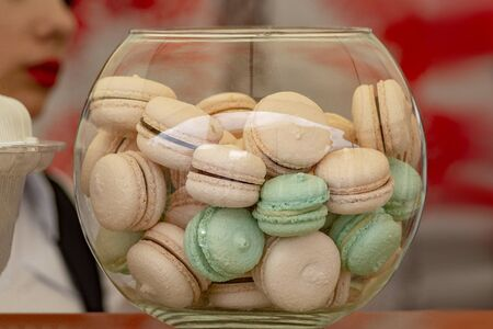 A vase of macaroons on a counter by a street vendor. Front view.
