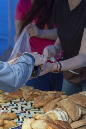The buyer pays by cashless payment using a smartphone (NFC) for pies purchased from a street food seller. Back view. Stok Fotoğraf - 133322305
