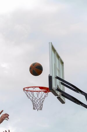 People play basketball outdoors. Hands in the frame. The ball flies into the basket. Vertical shot. Bottom view.