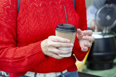 A girl in a red sweater holds a glass with a drink and a straw at a celebration on a street food court. Stok Fotoğraf