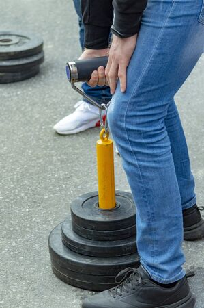 A teenager lifts weights in open air competitions. Side view.