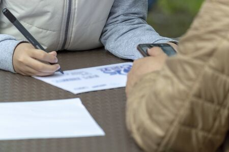 The child draws with a felt-tip pen on a sheet of paper lying on the table. On the contrary, an adult holds a smartphone. Front view. Stok Fotoğraf