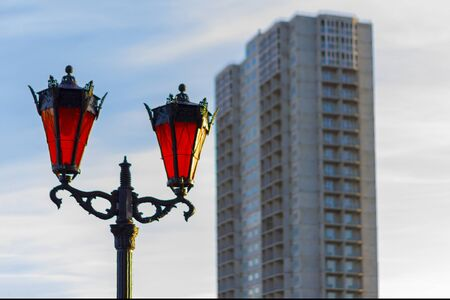 Street lamps twin with orange glass in the afternoon against the background of a high-rise residential building under construction. Front view.
