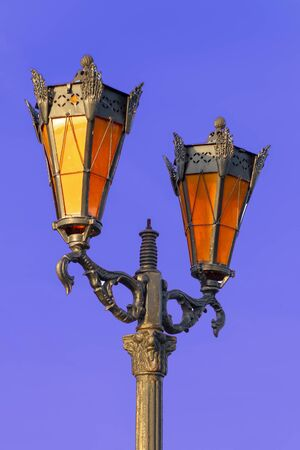 Street lamps twin with orange glass in the afternoon. Isolate on a blue background. Front view.