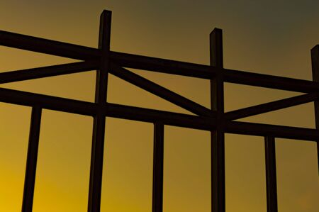 A metal fence made of square bars in the setting sun. Concept. Bottom view along.