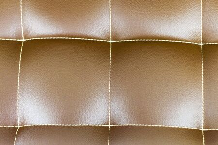 Part of the seat of a brown leather sofa. Stitching with squares. View from above. Stok Fotoğraf - 133322428