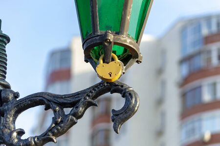 Yellow metal padlock on lamppost in park in honor of love of girl and guy. View from below. Stok Fotoğraf - 133322436