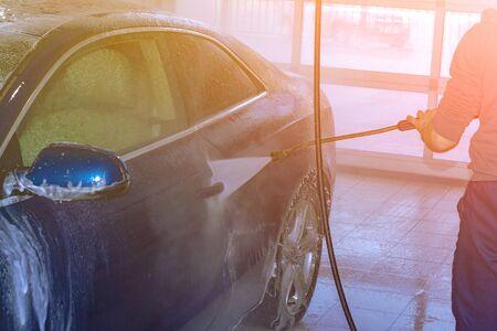 A car wash worker washes a blue car with a high-pressure apparatus. Foam. Rear side view. Stok Fotoğraf