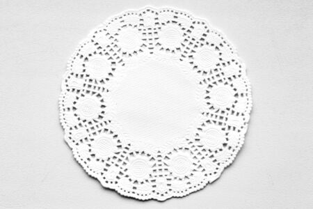 White decorative paper round napkin on a white-gray background. View from above. Stok Fotoğraf - 133322536