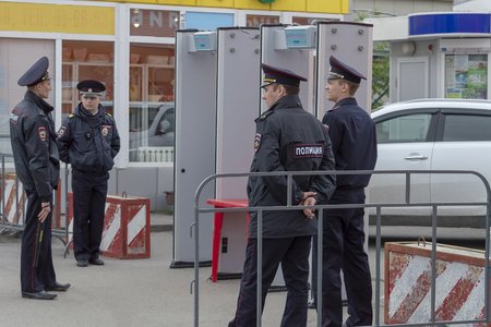 Four policemen in uniform are standing near the frames of a metal detector at a holiday, protecting public order. Side view. Surgut, Russia - June 12, 2019.