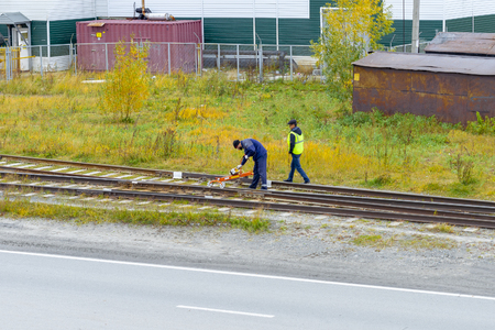 Two railroad workers are rolling the rails on a diagnostic trolley and checking the condition of the rails. Surgut, Russia - October 10, 2019.
