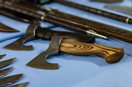 Two small axes with wooden handles on a table among knives and sabers. Close-up. Front view from above. Banco de Imagens