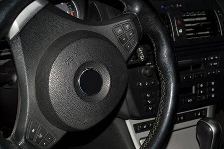 Wnętrze samochodu ma ciemny kolor. Widok przez drzwi wejściowe. Fragment.