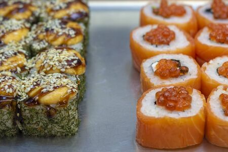 Two kinds of sushi rolls on metal plate. With eel and sesame seeds and red fish and chum salmon caviar. Front view.
