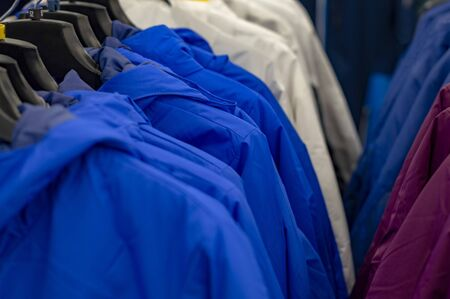 Several rows with top clothes on hangers. View from front. Stok Fotoğraf