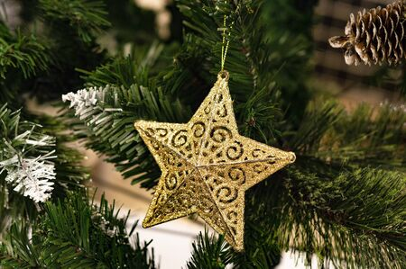 The star is a golden toy on the Christmas tree. A close-up view. Stok Fotoğraf