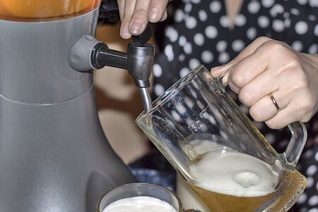 Woman pours fresh cold beer from a tabletop cooling dispenser into beer glasses. Indoors