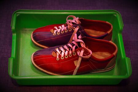 Multicolored leather shoes with laces, a pair, for playing bowling in a plastic tray