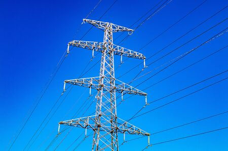 High-voltage power line and blue color metal prop with many electrical wires vertical view close up
