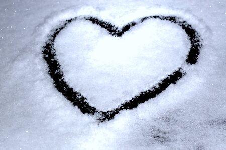 Heart drawn on a white, velvet, snow-covered glass Stok Fotoğraf