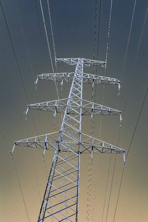 The support of the high voltage line in winter. View from below. Gradient sky. Vertical image.