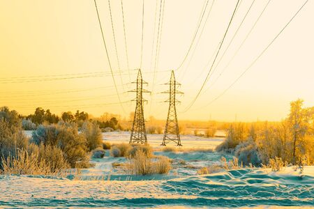 Two pillars of the high voltage line and wires through the riverplain in winter. Siberia.