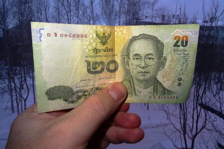 In hand of 20 Thai baht against backdrop of dark city in Siberia.