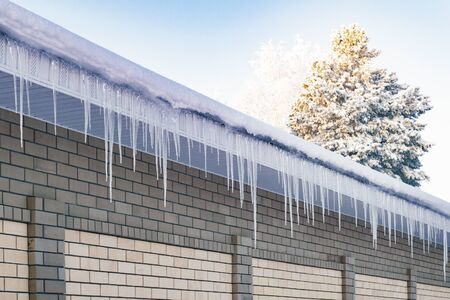 Ice icicles on the roof and the fence. The prospect is outgoing. Siberia.