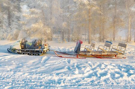 Snowmobile with sleigh in the winter forest. View from the side.