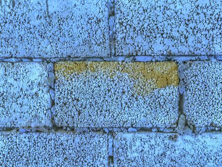 Brick wall is classic blue. One of bricks is defective with yellowness. Textural background. Front view.