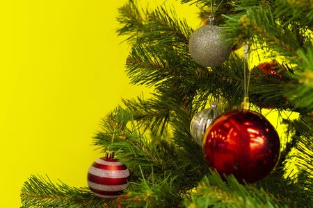 Part of the Christmas tree with balls of toys on a yellow background. View from the front. New Year.