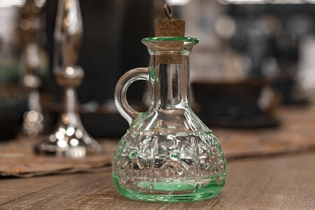Glass transparent carafe with cork on served table.