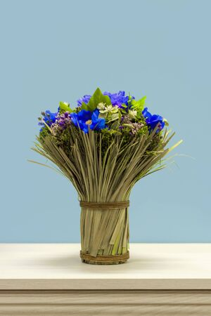 A bouquet of wildflowers tied with a rope on the dresser.