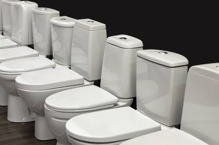 A row of white toilets. View from the side against a dark background.