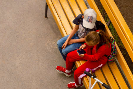 Children sit on bench with smartphone. Boy and girl. View from above. Surgut, Russia - 20 March 2020 Editöryel