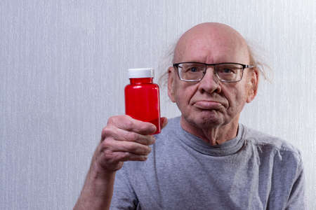 He's holding an empty pill jar in his hand. Portrait.