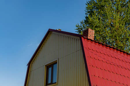 Attic red roof is made of metal from the house with a window. Outdoors of day. Back view.
