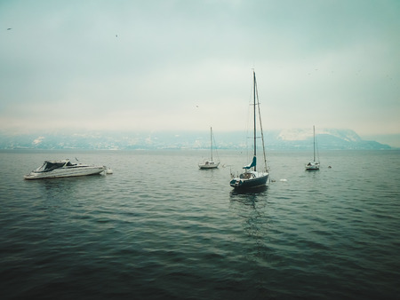 Small yachts on the lake in winter. Dull background.