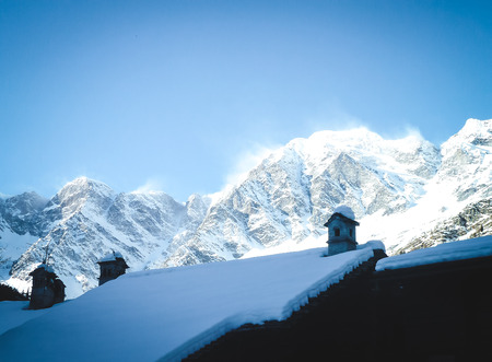 Beautiful winter scene. snow-covered roof on a background of mountains. Reklamní fotografie