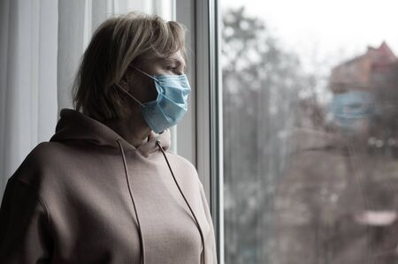 Portrait of senior caucasian woman in medical mask near the window watching outside. Self isolation concept.