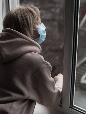 Senior caucasian woman with medical mask on her face looking through opened window