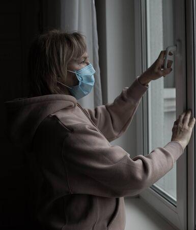Senior woman im medical mask opening the window. Self isolation during pandemic of coronavirus concept.