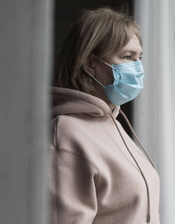 Portrait of senior caucasian woman in medical mask near the window watching outside. Self isolation concept. Standard-Bild
