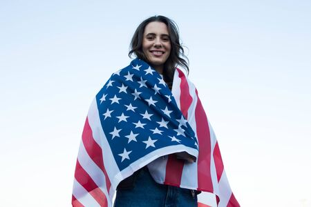 Outdoors portrait of caucasian woman covered with american flag. 4 july and Independence day of the USA concept.