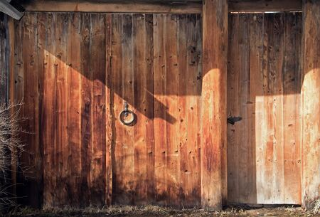 Old wooden gate with a metal handle. Dark orange wood background.