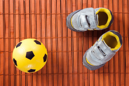 futbol infantil: Kids sneakers and soccer ball on a hardwood floor. The view from the top.